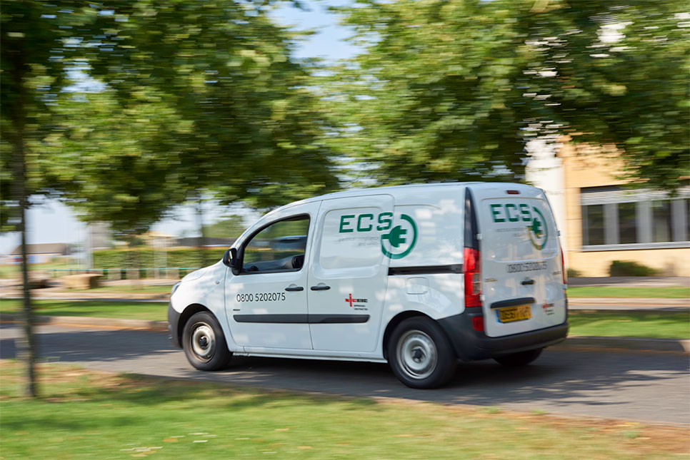 ECS work van driving through estate with branding along sides and back